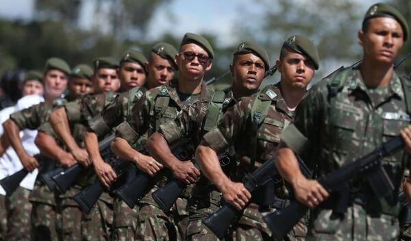 Alistamento militar: homens com armamento bélico em posição