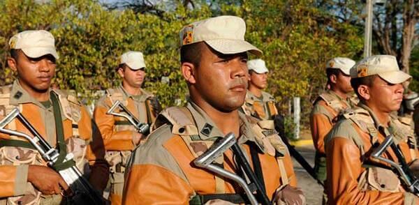 Homens brasileiros no exército segurando artefato bélico