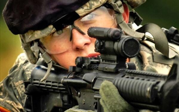 Mulher do exército brasileiro com material bélico em mãos