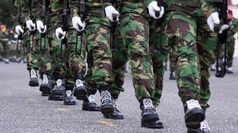 Homens do exército brasileiro marchando com farda e bota