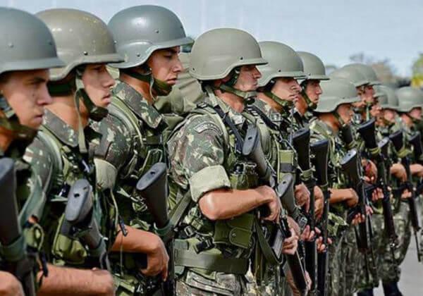 Homens brasileiros do exército com instrumentos bélicos